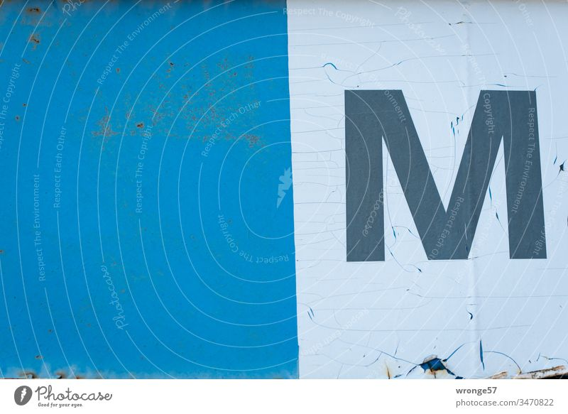 """Capital letter M on white foil on a blue gate Letters (alphabet) Colour photo Day Characters Exterior shot Building Orientation Old weathered surface,"""" blotchy"""