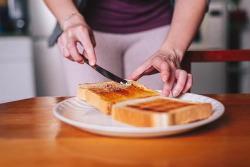 two hands spreading butter on toast plate breakfast knife food kitchen morning meal margarine widener organic snack bread human whole freshness piece