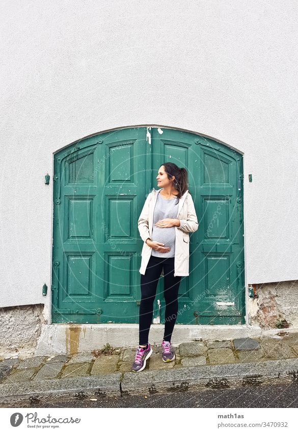 Young pregnant woman in front of a green door Pregnant youthful Woman Green Door Baby bump