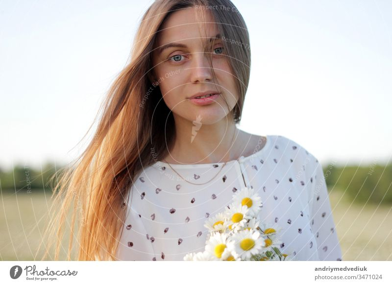 Beautiful young woman enjoying a field of daisies, beautiful girl relaxing outdoors, having fun, holding bouquet of daisies, happy young lady and spring-green nature, harmony concept.