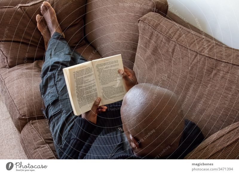 Black man, of African ethnicity, reading on the sofa 40s Caribbean adult african american black book british casual comfort comfortable concept couch down