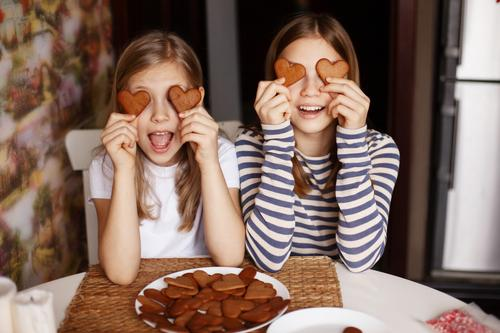 Charming, funny and laughing girls hold heart-shaped cookies, close their eyes and fool around. Valentine's Day and Women's Day cute kitchen female baby bakery
