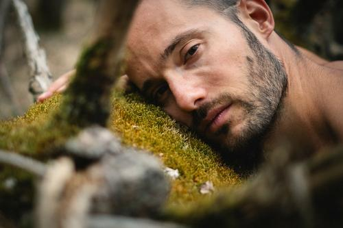 Portrait of a man lying on a tree trunk with moss in the forest and looking sad, melancholic, serious, vulnerable into the camera Man Tree Tree trunk Moss