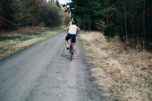 Young man on a bicycle riding a road through the forest Bicycle Cycling cyclist Man Freedom Summer Street off Forest Sports Exterior shot Leisure and hobbies