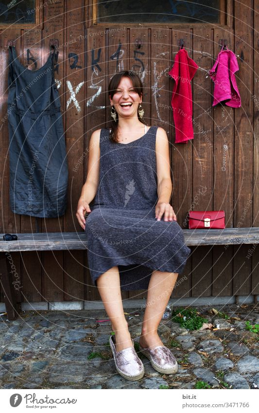 Young woman sits laughing on a bench, in front of a wooden wardrobe with a dress and towels hanging on it. Woman Youth (Young adults) girl Human being teenager