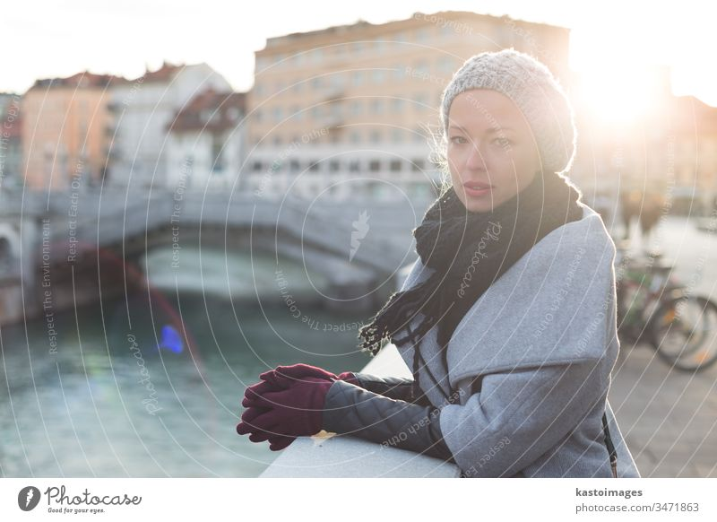 Thoughtful woman outdoors on cold winter day. beautiful girl portrait female lady city Ljubljana lifestyle beauty river sun attractive caucasian autumn person