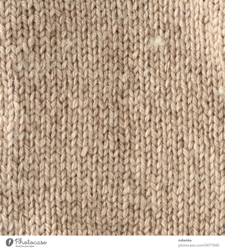 fragment of knitted fabric from light brown wool of a sheep beige yarn backdrop background canvas closeup cloth clothes clothing color craft decor decorative