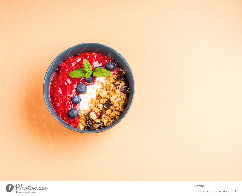 Yogurt bowl with raspberries on peach orange pastel granola oat healthy delicious concept smoothie blueberries blended yogurt background breakfast cantaloupe