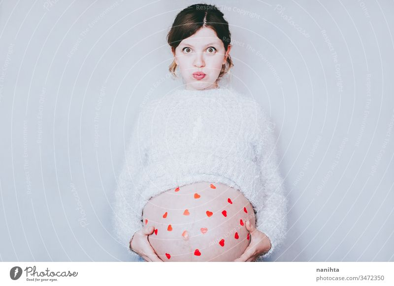 Young happy mom with a lot of red hearts in her tummy pregnant pregnancy life happiness belly woman mother family motherhood fun funny creative healthy month