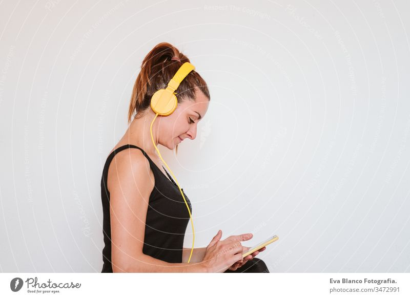 Young woman listening to music on yellow mobile phone and headset. Sitting on yoga mat, relaxing after exercise. Healthy lifestyle indoors technology internet