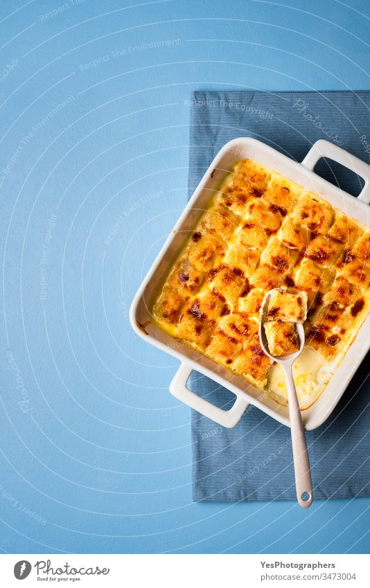 Cheese gnocchi in ceramic oven tray. Italian pasta with melted cheese baked food blue background cheese gnocchi cooked cream sauce dinner dumplings european