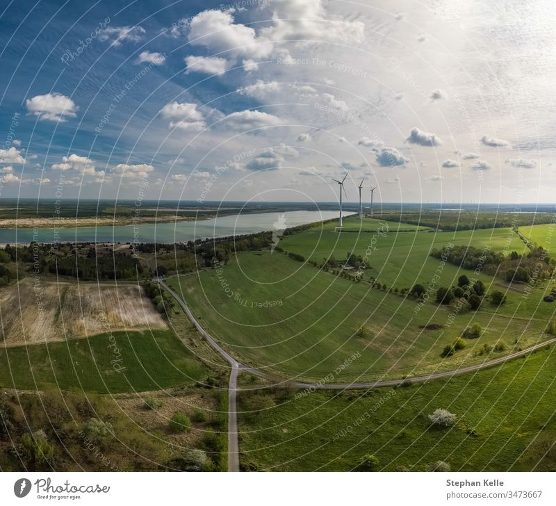 Alternative energy - wind generator wheels in backgroud of an aerial nature with fields and a lake. environment winning alternative green chance sky drone