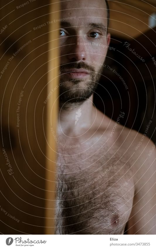 A man with naked upper body, looking out behind a wooden door directly into the camera Man Upper body free Chest Naked Wooden door look into the camera