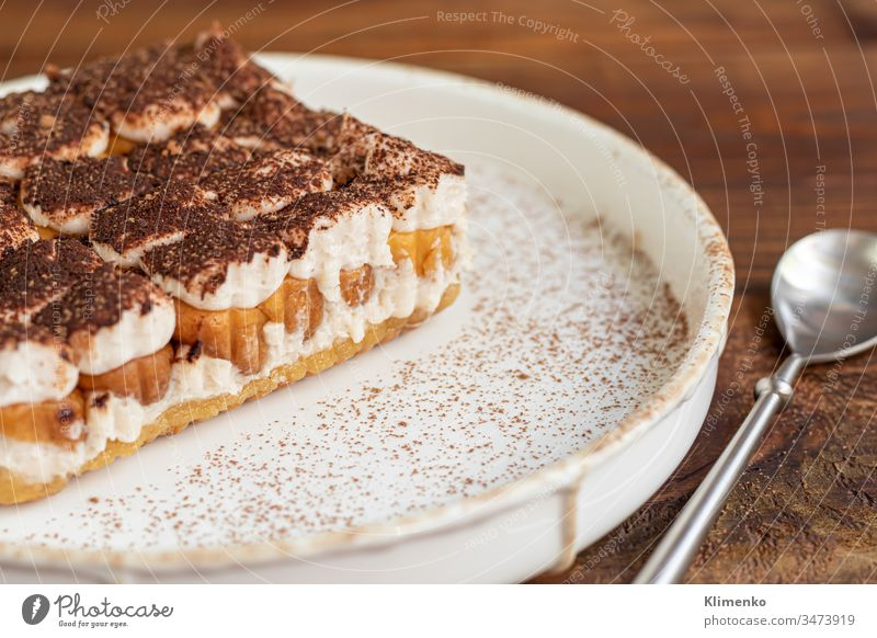 Tiramisu. Traditional italian dessert on wooden background. Garnished with a sprig of mint, lime slices. In a transparent cup, tea with sea buckthorn. tiramisu