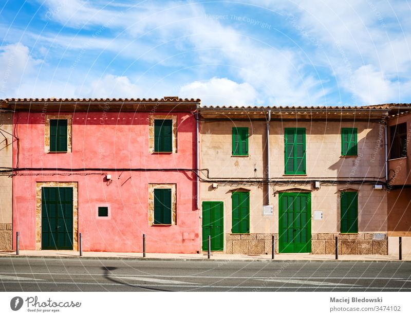Old buildings with wooden shutters by a street in Alcudia, Mallorca. old house Spain window wall door architecture facade closed town sunny empty nobody bench