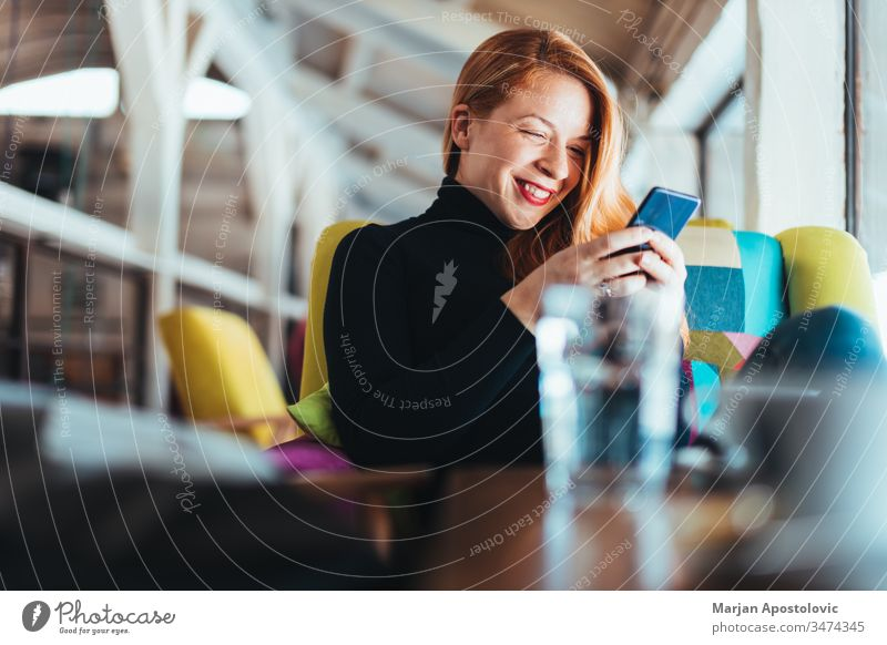 Young happy woman using smartphone in a cafe young smile indoor casual smiling table sitting lifestyle connected connection mobile massaging communication