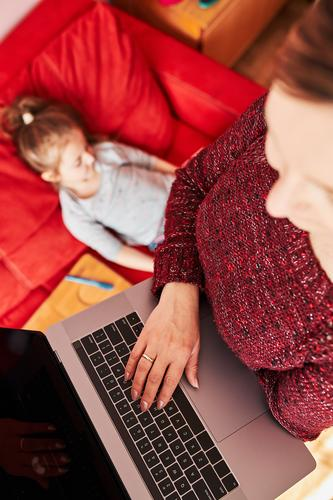 Woman mother working doing her job remotely during video chat call stream online course webinar on laptop from home during COVID-19 quarantine while her daughter watching video on tablet. Woman sitting on bed in front of computer looking at screen