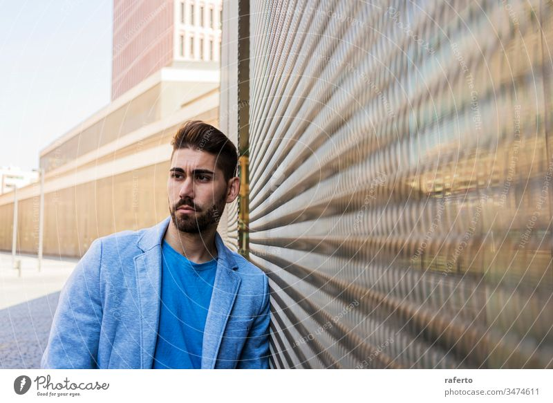 Young bearded man, model of fashion, in urban background wearing casual clothes while leaning on a wall and looking aside cool style portrait guy 1 photogenic