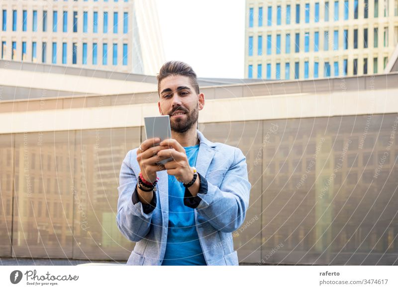Portrait of Handsome bearded young man smiling when he is using his mobile phone style guy sunglasses hipster 1 photogenic technology writing adult standing