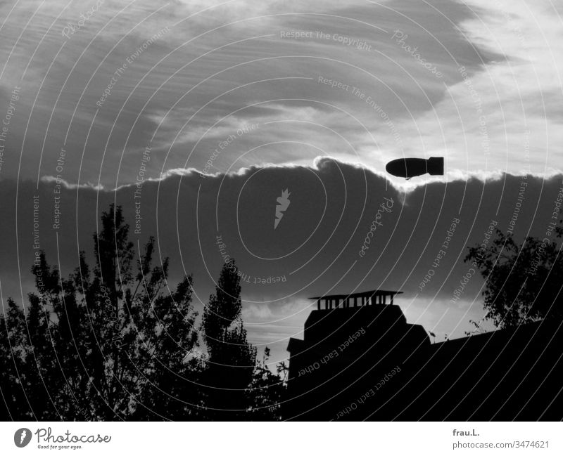 When she saw the zeppelin over the roofs and trees of the city, she thought of Radziwill. Town Zeppelin Clouds Sky Sunset House (Residential Structure) Twilight