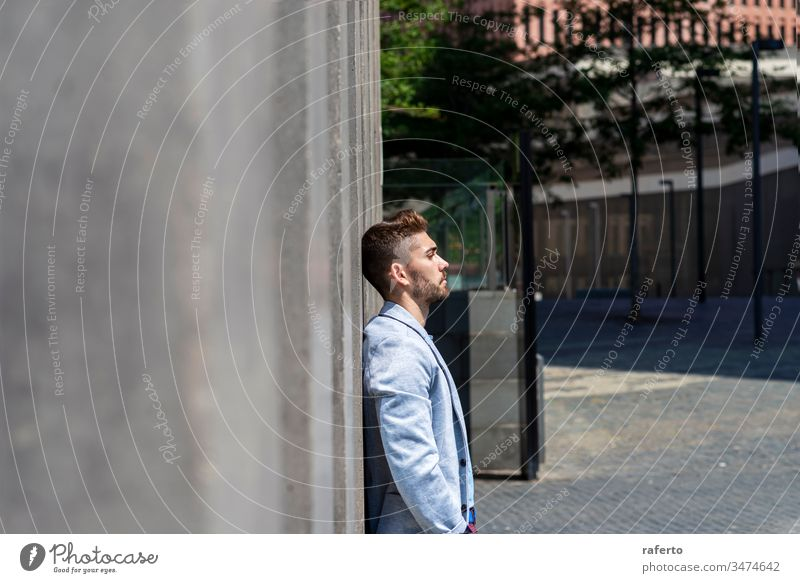 Pensive young bearded man looking away in the street while leaning on a wall outdoors uncertainty businessman thinking disappointment overworked professional