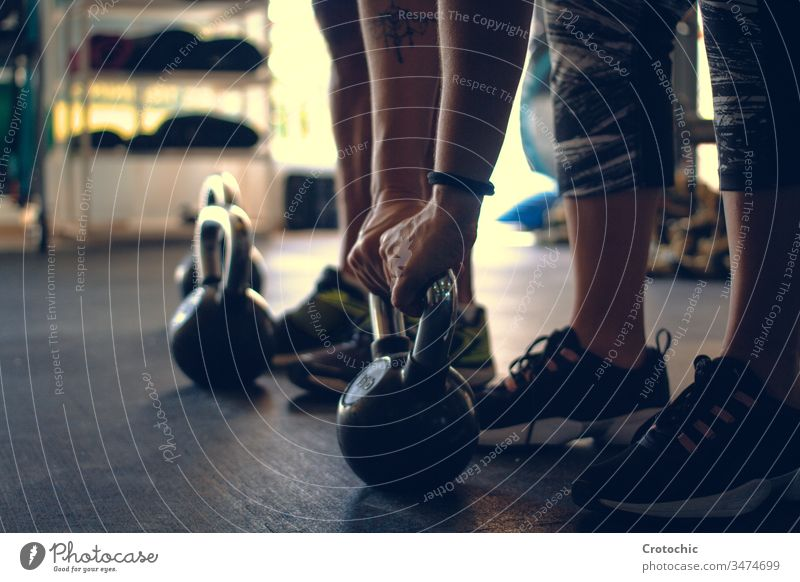 Detail of a man holding a kettlebell placed on the floor of a gym athlete weights determination exercising indoors lifestyles strength vitality wellbeing people