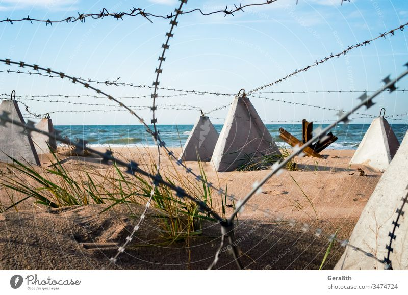 barbed wire and concrete military fence on the beach near the sea in Crimea Russia Ukraine annexation army ban barrier blue border closed closed territory