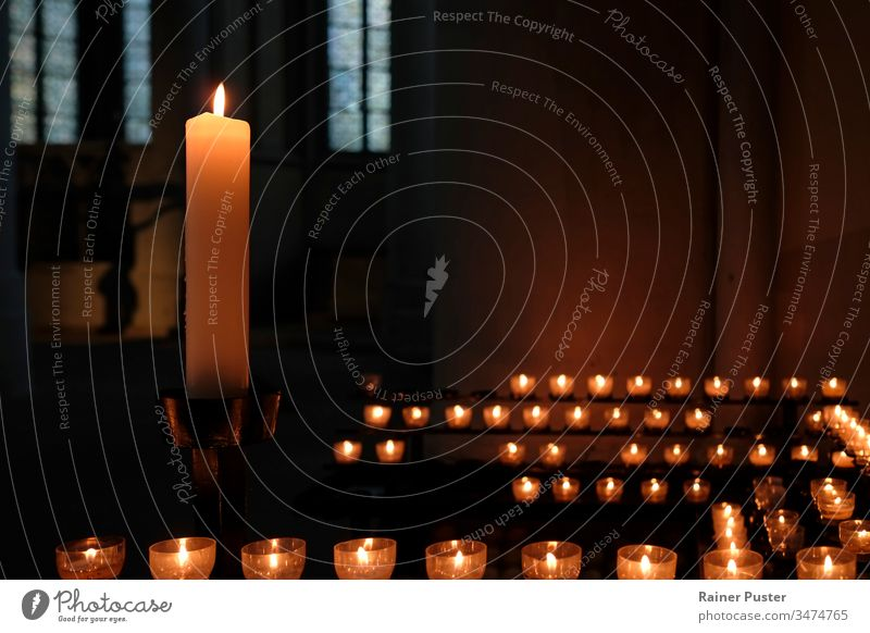 One large candle and many small candles in a church candlelight inside a church religion faith belief religious Religion and faith christianity hope prayer