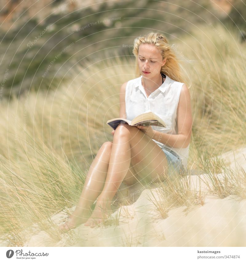 Woman reading book, enjoying sun on beach. summer woman nature free happy carefree relax wind freedom happiness relaxation leisure island young wellness