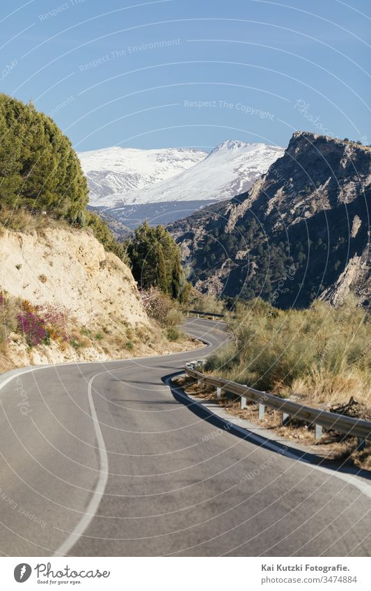 Road through the Spanish Sierra Nevada with snow-covered mountains in the background Andalucia Street Mountain Snow Snowcapped peak Spring Spain Curve
