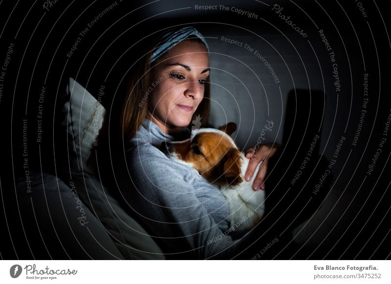 young woman at home using mobile phone. cute jack russell dog lying with her. Night time night screen dark pet relax together love friendship technology