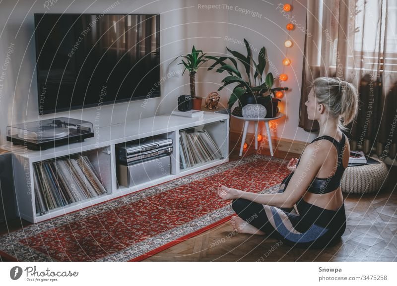 Young woman meditating in the living room. Staying healthy at home. attractive beautiful beauty boho chic boho interior calm care comfortable exercise female