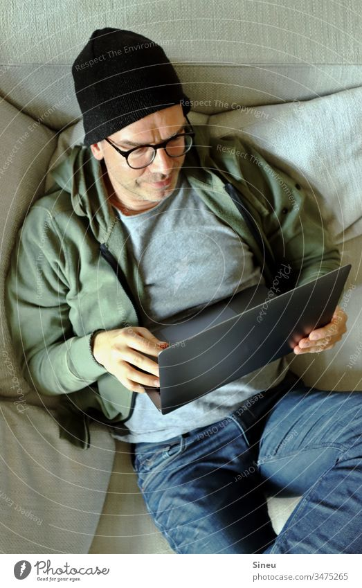 HomeOffice: relaxed man lying on the sofa with his notebook home office Workplace Notebook Sofa cap Hipster Jeans Eyeglasses Easygoing casually Man independent