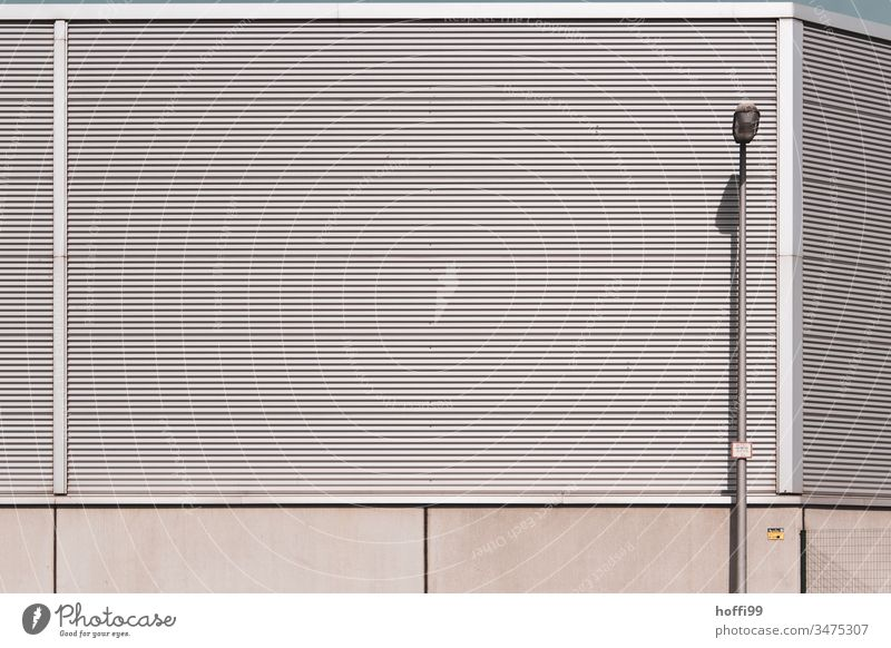monotone metal facade with street lamp Warehouse Storage Hall Industrial Photography Corrugated iron wall Corrugated sheet iron corrugated sheet metal facade