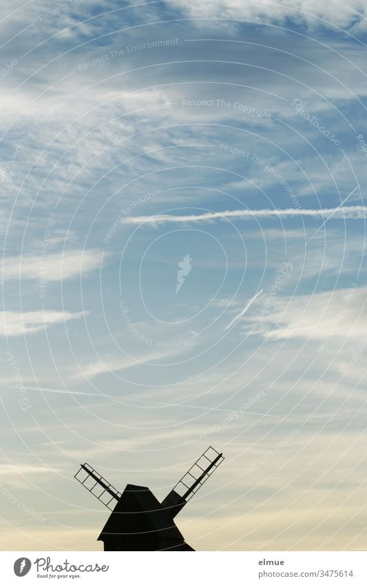 Windmill at the lower edge of the picture in silhouette form and sky with contrails bock windmill Vapor trail Wood fair weather cloud Grand piano Romance