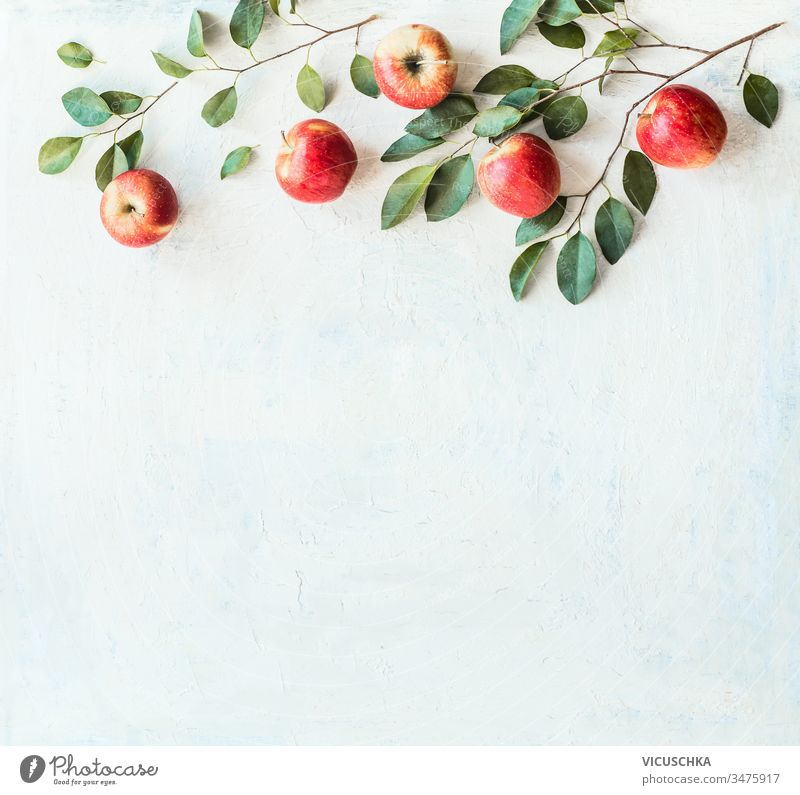 Tasty ripe red apples with branches and green leaves on rustic white background, top view. Border or frame with copy space for your design tasty border