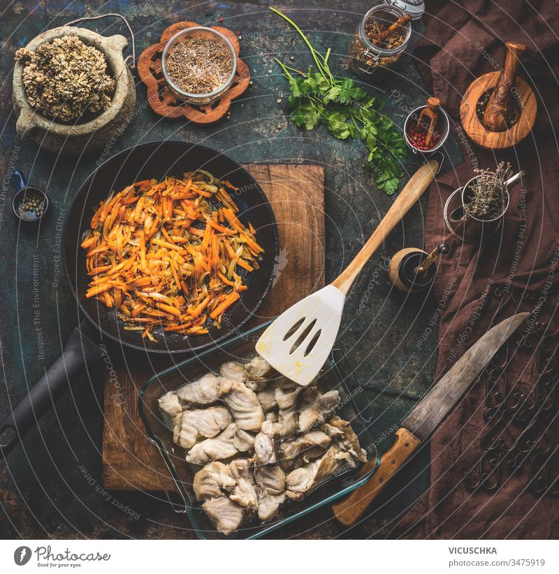 Preparation of coal fish dish and vegetables sauce on dark kitchen table background with ingredients, top view. Healthy home cooking concept. Homemade cuisine