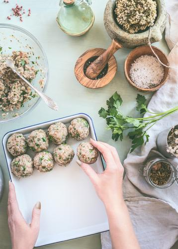 Female hand make buckwheat balls on kitchen table background with herbs and spices, top view. Healthy homemade food female healthy appetizer cook cooking