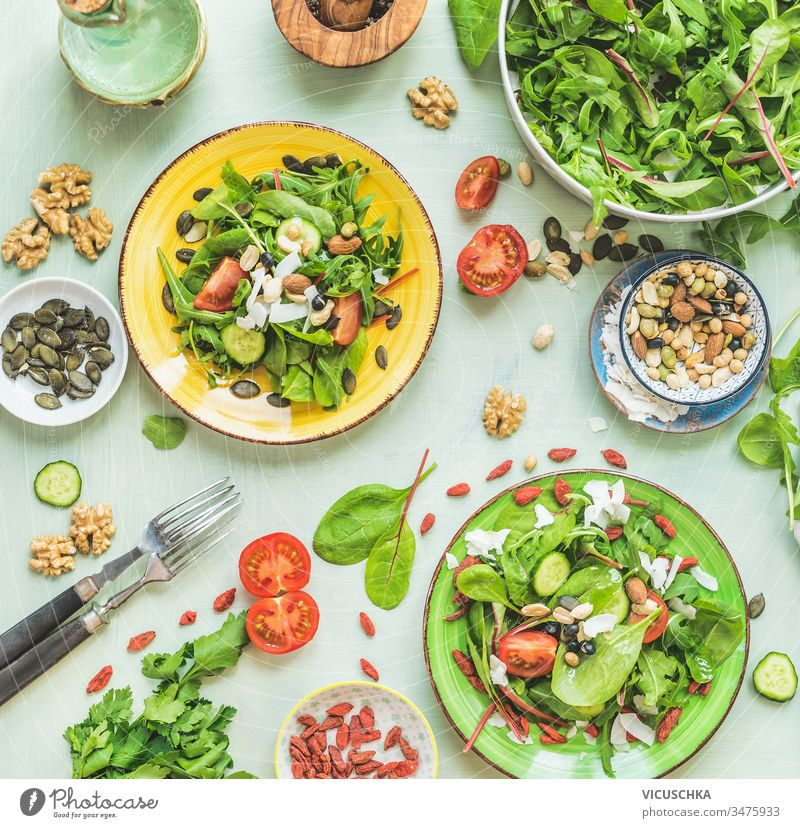 Plates with green salad on kitchen table background with forks and ingredients: nuts, seeds, young leaves, olives oils dressing. Top view. Dieting. Summer cuisine. Healthy home food