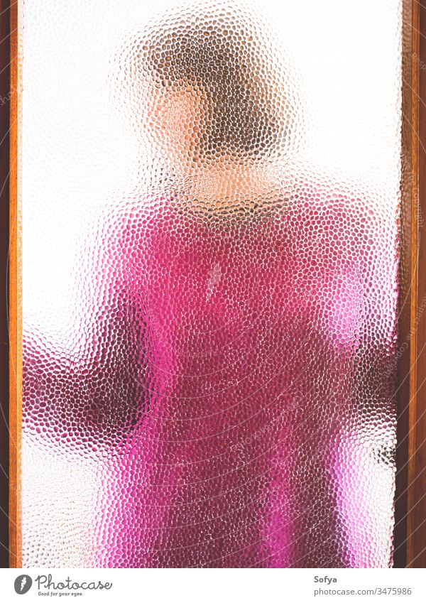 Young woman behind closed door seen through glass girl stay home window silhouette pink sweater winter cozy stay safe coronavirus covid19 isolation alone