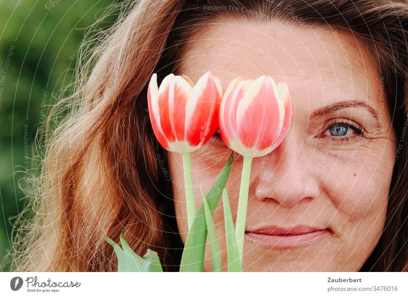 Portrait of a beautiful woman, who is happy about spring, with two tulips in front of her right eye, portrait smile Woman Joy already Face Eyes Human being luck