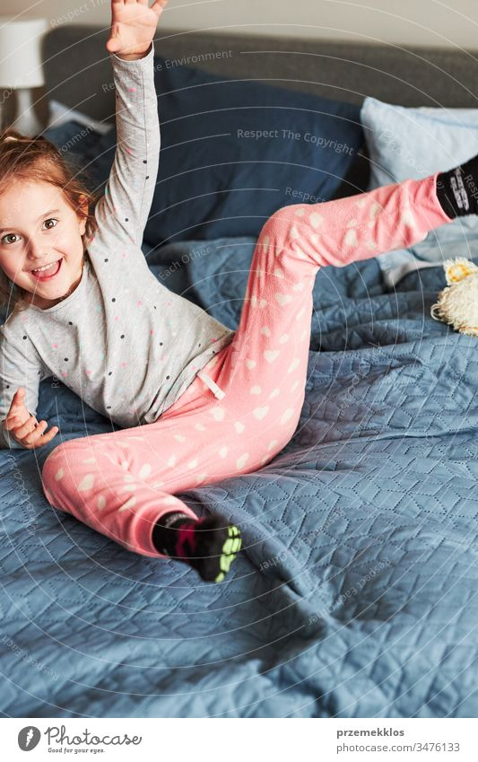 Little happy playful kid girl having fun making silly funny faces jumping on bed in bedroom in the morning at home playing childhood joy cute laughing smiling