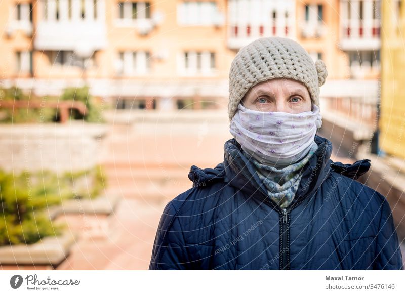 A poor elderly woman wears a homemade mask to protect herself from viruses adult airborne breathing buildings city contagion contagious corona coronavirus cough