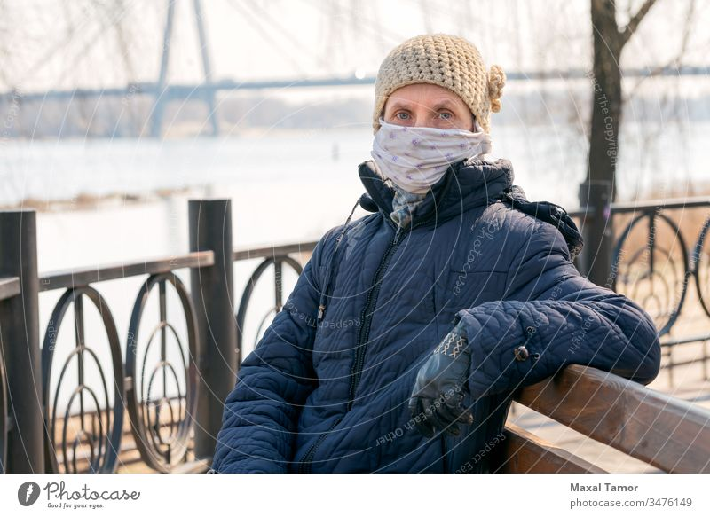 A poor elderly woman wears a homemade mask to protect herself from viruses adult bench breathing coat contagion contagious corona coronavirus cough country