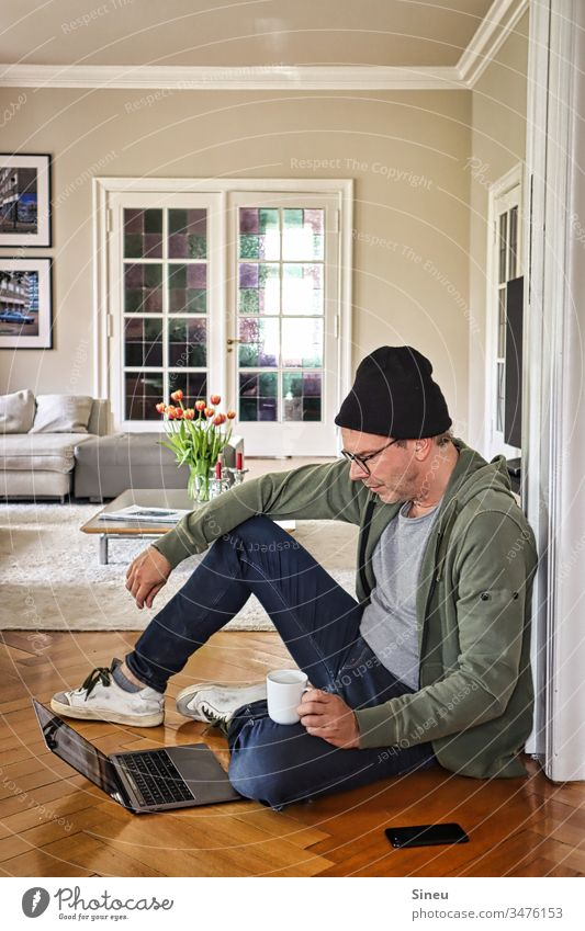 HomeOffice: relaxed man sitting on the floor in front of his notebook and drinking coffee Living room Home office Man Only one man Mid adult man Eyeglasses