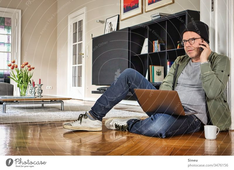 HomeOffice: the relaxed man is sitting on the floor in front of his notebook again and is looking forward to his office Living room work from home Home office