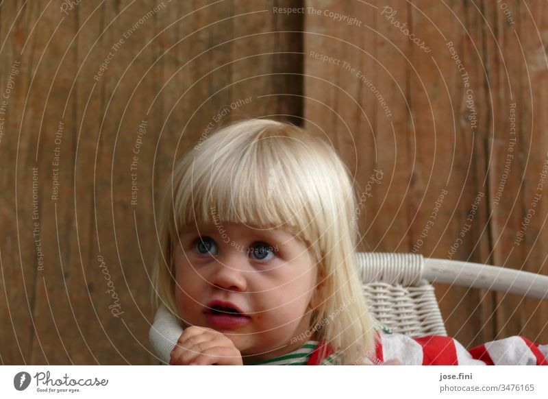 Little girl sitting on a chair and looking up with big blue eyes Portrait photograph Day Natural Love Blonde little girl Child big eyes conversation eloquent