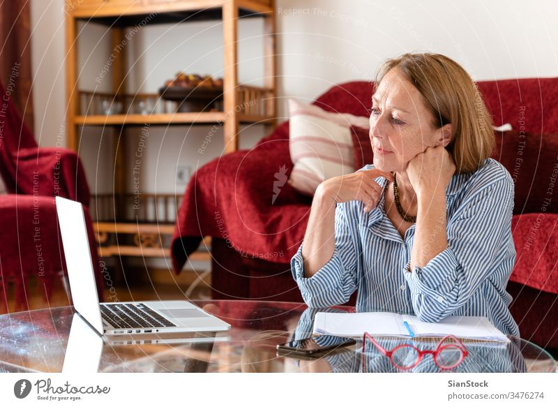 Middle age senior woman smilling while using computer female laptop mature people one house person lifestyle eyeglasses conversation attractive relax work