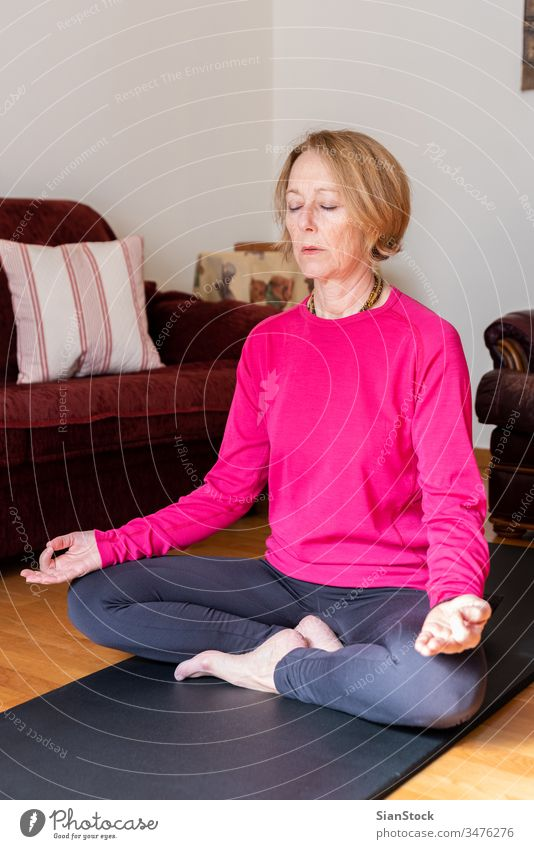 Middle aged woman sitting in lotus position on yoga mat in her living room. meditation lotus pose beauty workout european exercising flexibility wellness single