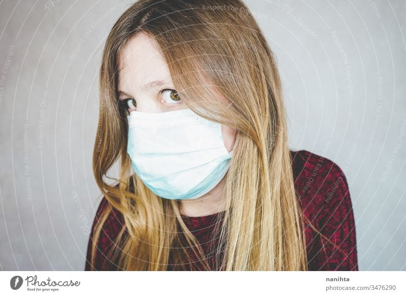 Young woman wearing a protective face mask covid 19 flu influenza coronavirus pandemic epidemic illness respiratory illness social distance contagion risk